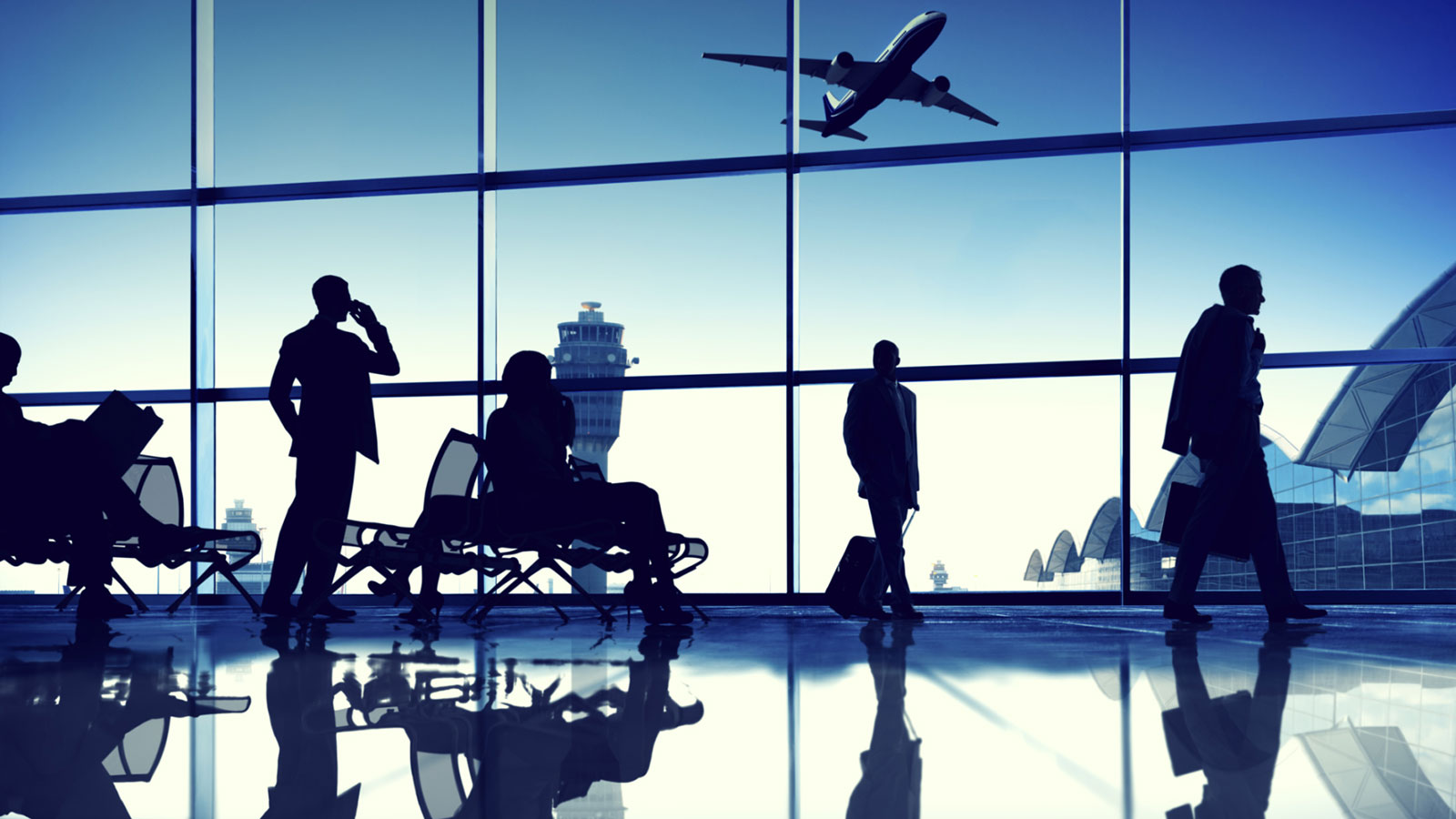 Travelers in an airport lounge with airplane taking off