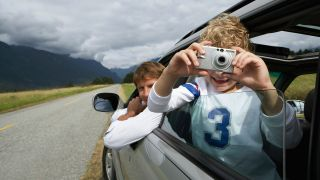 Boy taking photo out of car
